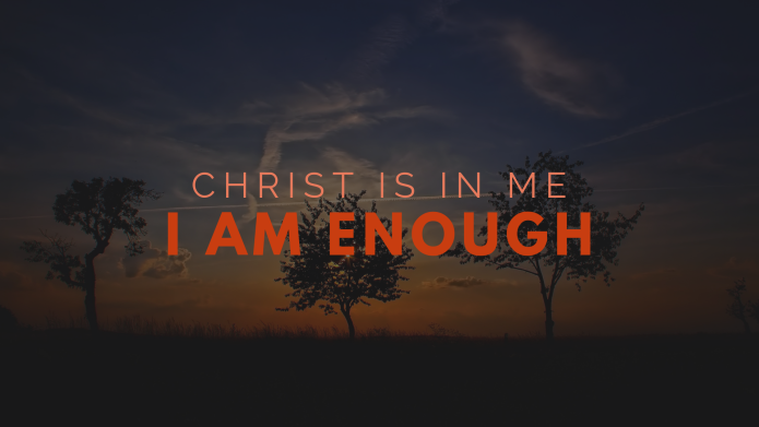 "In bold red and coral lettering the text say ""Christ is in me, I am Enough"". In the darkened background three trees stand with the sun just setting."